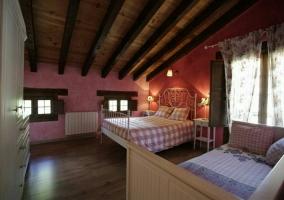 Dormitorio en tonos rosas con techos abuhardillado