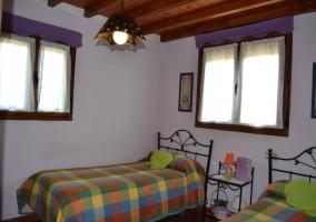 Dormitorio doble con colchas de colores y ventana