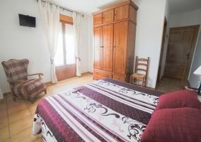 Dormitorio de matrimonio con armario de madera y ventana