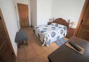 Dormitorio de matrimonio con cabecero y mesillas de madera