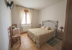Dormitorio de matrimonio con tele delante de la cama