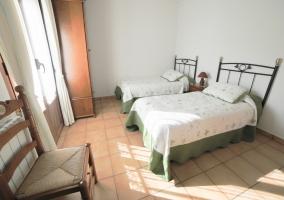 Dormitorio doble con camas individuales y detalles en verde