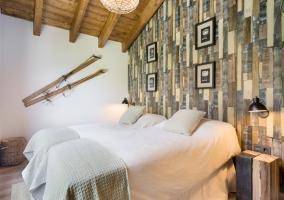 Dormitorio doble con varios cuadros en la pared