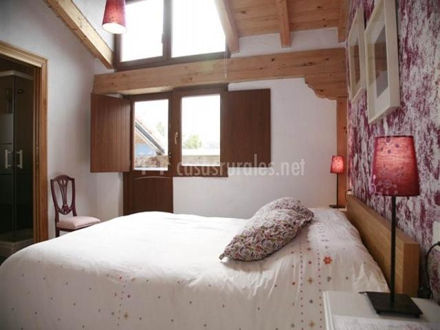 Habitación  con detalles en rosa y techos de madera