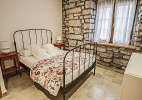 Dormitorio de matrimonio amplio con paredes de piedra