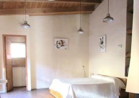 Dormitorio de matrimonio con un cuadro en la pared