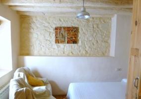 Dormitorio de la casa con pared en piedra