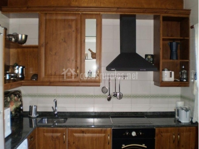 Cocina con vitrocerámica y  muebles de madera