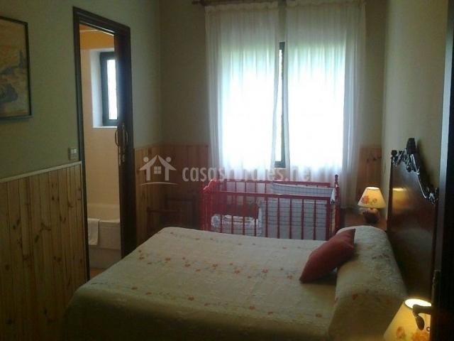 Habitación con cama de matrimonio, baño y cuna