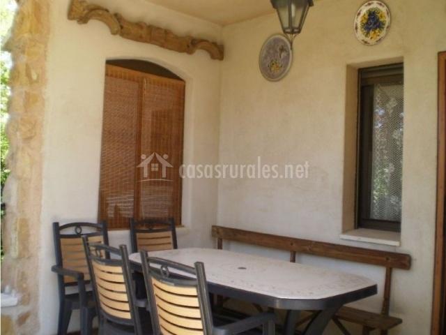 Porche de la casa rural con mesa y sillas y un banco de madera