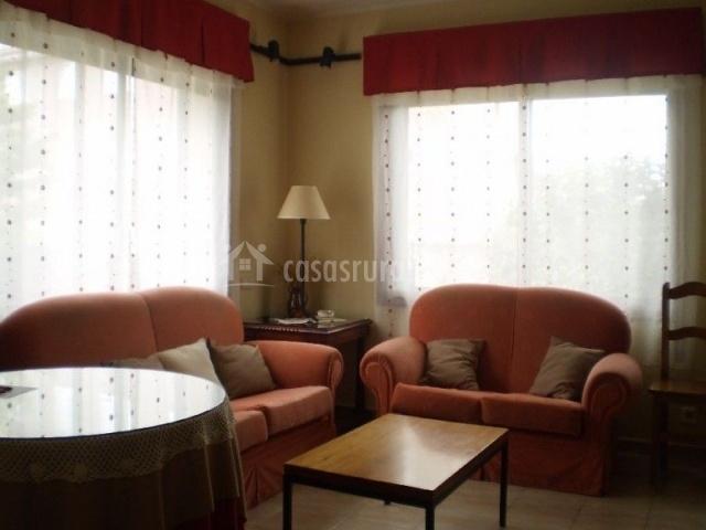 Salón-comedor con mesa camilla y ventanales