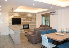 Sala de estar amplia con sillones y mesa de comedor en madera