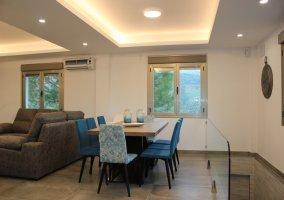 Sala de estar y la zona de comedor con sillas azules