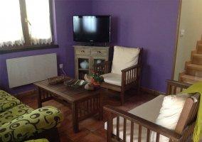 Sala de estar con paredes moradas y sillones