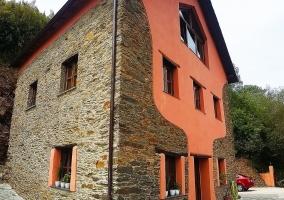 Acceso a la casa con fachada en naranja y piedra