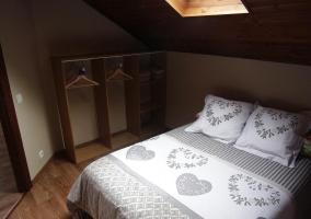 Dormitorio de matrimonio con techos abuhardilllados