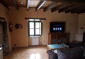 Sala de estar con tele de plasma y una ventana