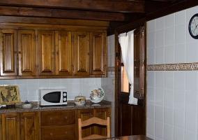 Cocina con armarios y mesa de madera