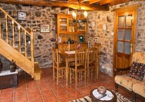 Sala de estar con la mesa de madera y paredes de piedra