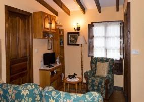 Sala de estar con los sillones tapizados y la tele al lado