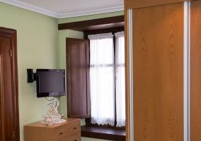Dormitorio y tele junto a la ventana