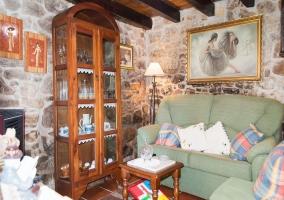 Sala de estar con sillones en verde y pared de piedra