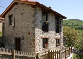Acceso a la casa con fachada en piedra y valla de madera