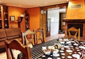 Sala de estar con mesa y chimenea en el centro