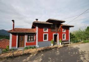 Acceso a la casa con fachada en rojo