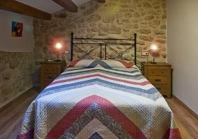 Dormitorio de matrimonio abuhardillado con pared de piedra