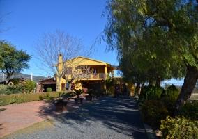 Acceso a la casa con la fachada amarilla