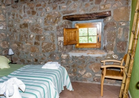 Dormitorio doble con detalles verdes y toallas