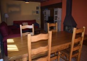 Sala de estar con mesa de madera y chimenea