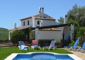Tumbonas con piscina y casa