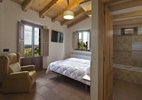 Dormitorio con camas individuales y vistas del aseo