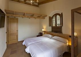 Dormitorio doble con la ventana sobre las camas