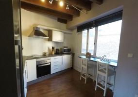 Cocina con armarios blancos y barra office