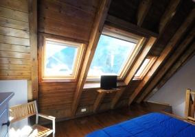 Dormitorio abuhardillado con mueble para la tele
