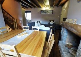 Sala de estar con mesa de comedor delante de la chimenea