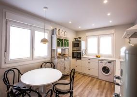 Cocina amplia con armarios en blanco