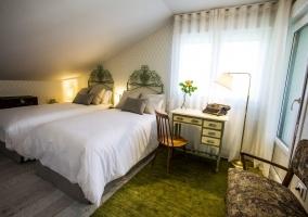 Dormitorio doble verde amplio con sillones
