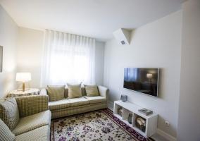 Sala de estar con sillones alargados y tele de plasma