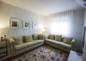 Sala de estar con sillones de cuadros y tele de plasma