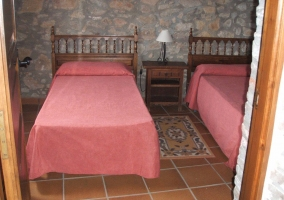 Dormitorio con un par de camas individuales y paredes de piedra