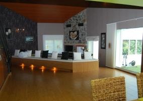 Sala de estar con las escaleras al lado y la cocina al fondo