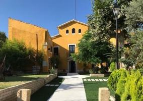 Acceso a la casa con caminos y fachada amarilla