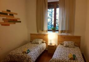 Dormitorio con un par de camas y ventana