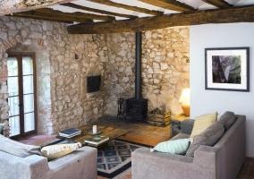 Sala de estar con chimenea de forja y pared de piedra