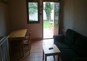 Sala de estar con mesa de madera y cocina