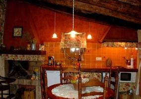 Cocina comedor con chimenea y mesa de madera